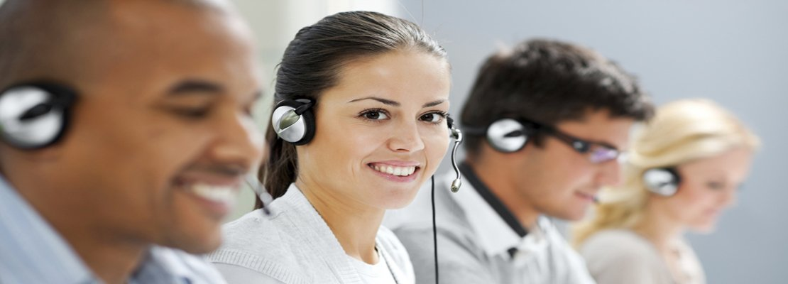 Group of confident young customer service agents with headset. The focus is on the brunette female looking at camera.